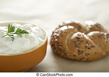 Bowl with cream cheese and one bagel