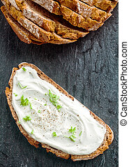 Cream cheese with herbs and seasoning on a slice of fresh ...