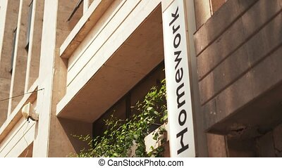 Cream-colored building covered by the sunlight with a white 'Homework' sign next to some hanging plants