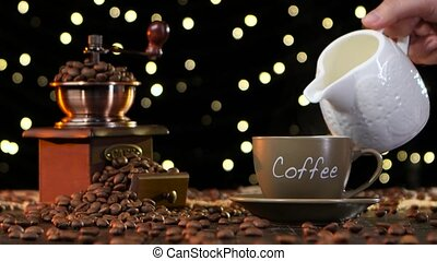 Cream is added to cup of hot coffee or tea, brown small cup...