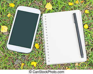 cream notebook with pen and mobile phone on green grass