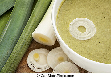a bowl of leek cream soup with green fresh leeks
