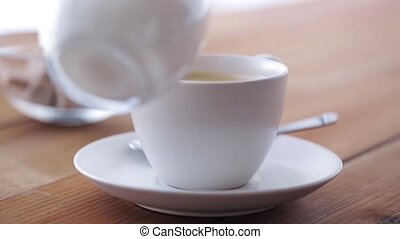 cream or milk pouring to coffee cup on table - breakfast,...