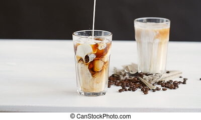 Cream poured into a iced coffee cocktail on a white table