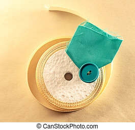 Cream ribbon in roll with blue button