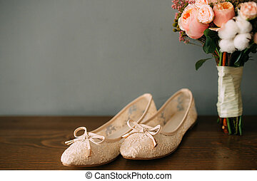 Cream shoes of the bride on green on a wooden table table