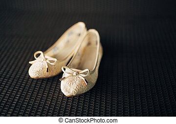 Cream shoes of the bride on the green on a black background