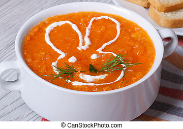 cream soup of carrots for children with bunny close-up -...