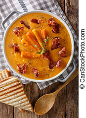 Cream Soup of sweet potato with bacon in a saucepan and toast close-up on a table. Vertical top view