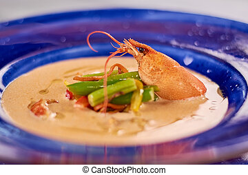 Cream soup with crayfish tails and vegetables.