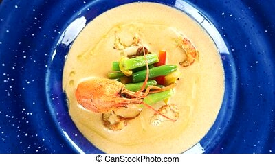 Cream soup with crayfish tails. Garnished food top view.