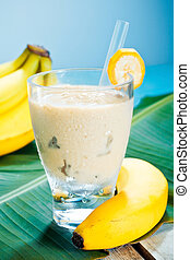 Creamy banana smoothie blended with fresh yoghurt in a glass with ripe bananas and a banana leaf