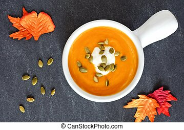 Creamy butternut squash soup topped with pumpkin seeds and cream on slate background with autumn leaves