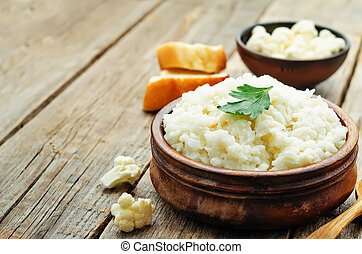 creamy cauliflower garlic rice on a dark wood background....
