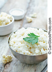 creamy cauliflower garlic rice on a white wood background....