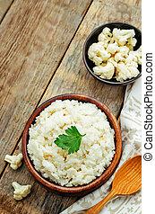 creamy cauliflower garlic rice on a dark wood background....