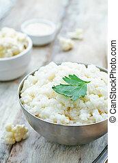 creamy cauliflower garlic rice on a white wood background....