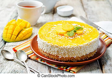 creamy mango mousse cake on a white wood background. toning...