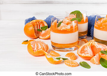 Creamy panna cotta with orange jelly in beautiful glasses, fresh ripe mandarin, blue textile on white wooden background. Delicious Italian dessert. Closeup photography. Selective focus.
