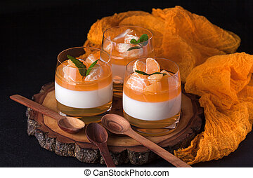 Creamy panna cotta with orange jelly in beautiful glasses,...