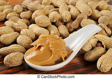 A spoonful of creamy peanut butter with peanuts in the shells in the background