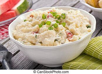 A delicious homemade creamy potato salad on a rustic picnic table.