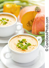 Creamy pumpkin bacon soup with green onion in two white...
