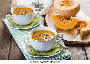 Creamy pumpkin soup for Christmas decorated with seeds