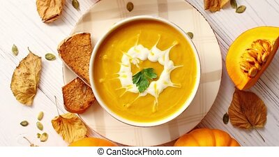 Creamy pumpkin soup in bowl with herb - From above view of...