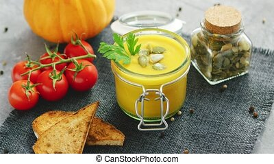 Creamy pumpkin soup in jar with bread and tomatoes - From...