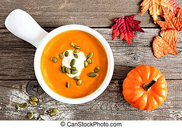 Creamy pumpkin soup topped with pumpkin seeds and cream on rustic wood background with autumn leaves