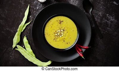 Creamy soup with green pea in a ceramic white plate -...