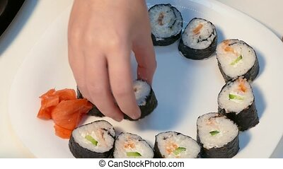 Create a set of sushi rolls. - Hands lay pieces of sushi...