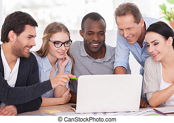 creatief, team, doorwerken, project., groep van zakenmensen, in, vrijetijdskleding, zitten samen, aan tafel, en, kijken naar, de, draagbare computer