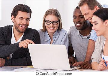 creatief, team, op, work., groep van zakenmensen, in, vrijetijdskleding, zitten samen, aan tafel, en, het bespreken, iets, terwijl, kijken naar, de, draagbare computer