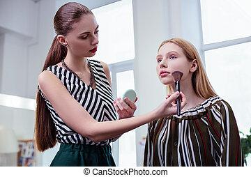 Nice long haired visagiste applying facial powder