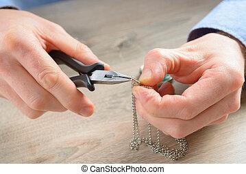 Creating or fixing jewelry - Man repairing or creating...