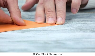 Creating origami, close up. Male hands and orange paper.