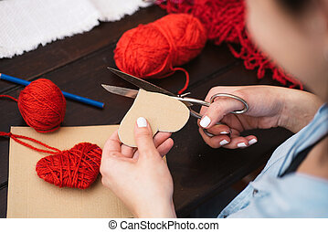 Creating red woolen heart - Woman creating red woolen heart