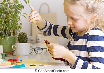 little girl sews toy