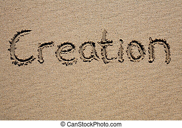 Creation, written on a sandy beach.