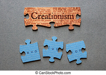 Creationism against background of Genesis text printed on matched jigsaw pieces with Evolution against background of human genome sequence printed on mismatched jigsaw pieces.