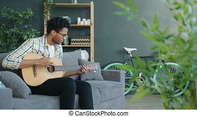 Creative Afro-American man playing the guitar and singing in leisure time at home