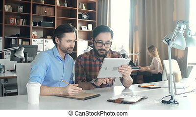 Creative Agency - Close up of two guys brainstorming on the...