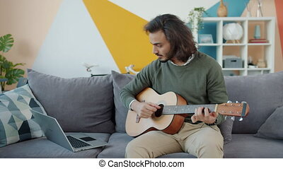 Creative Arab man playing the guitar and using laptop ...