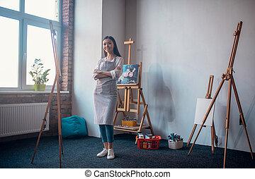 Joyful happy woman standing in the art studio