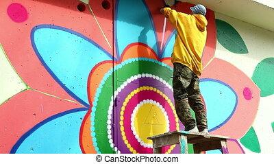 Creative art - man painting graffiti on wall