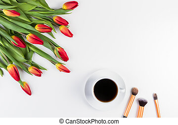 Creative background with make up brushes, cup of coffee and flowers on white background