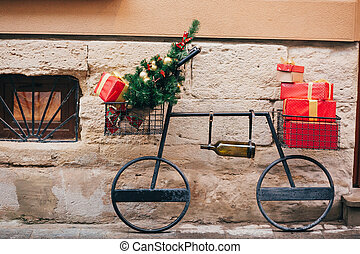 Creative bicycle with christmas tree, red presents, wine bottle in european city street. Stylish christmas street decor, Festive decorations and illumination. Winter holidays. Wine shop