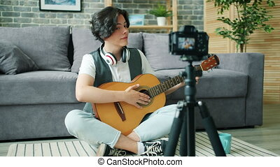 Creative boy recording tutorial about guitar for online vlog...